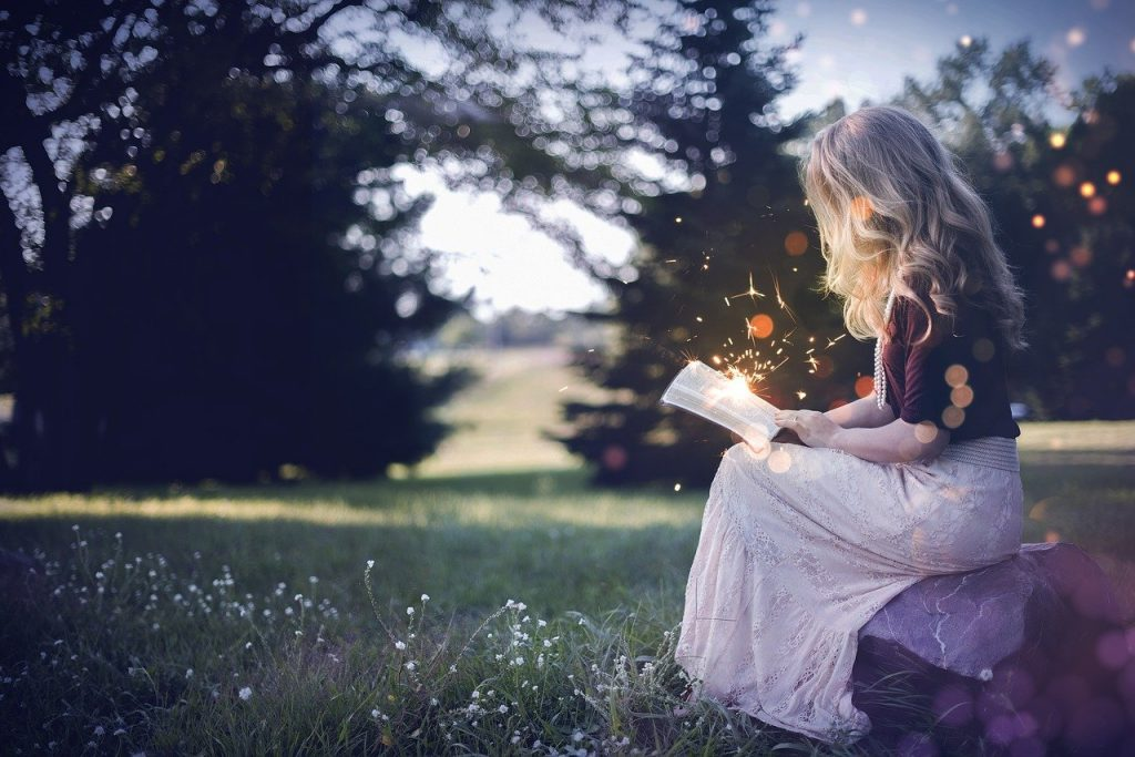 Young blonde woman sitting outside on grass reading a book with sparks coming out of it
