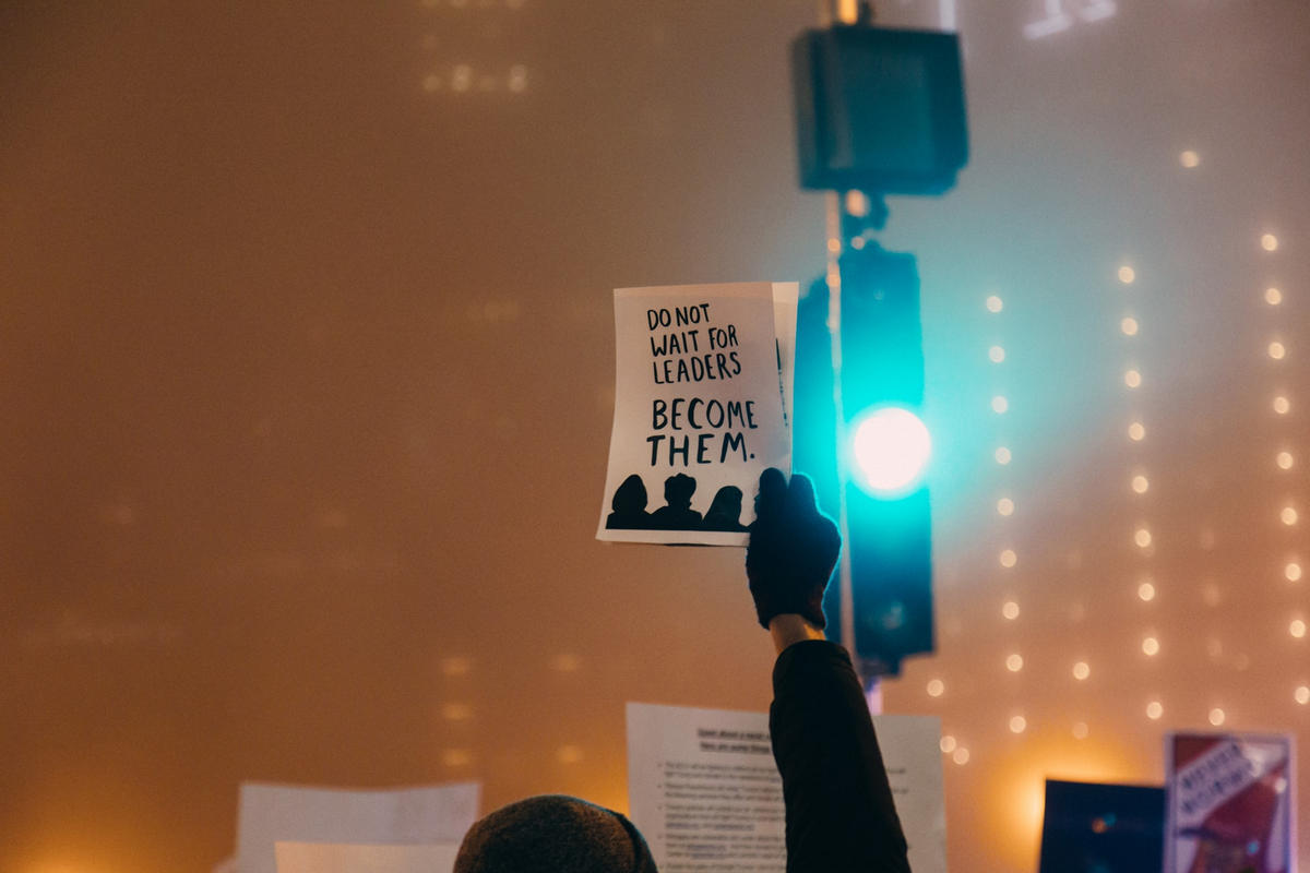 Someone holding up a sign with the text 'Do not wait for leaders, become them'