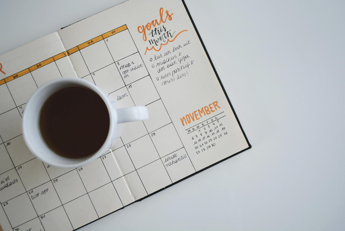 A coffee cup standing on a monthly diary