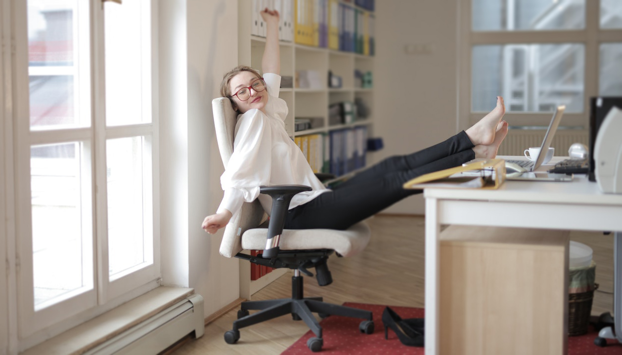 Woman at desk leaning back in chair relaxed and happy