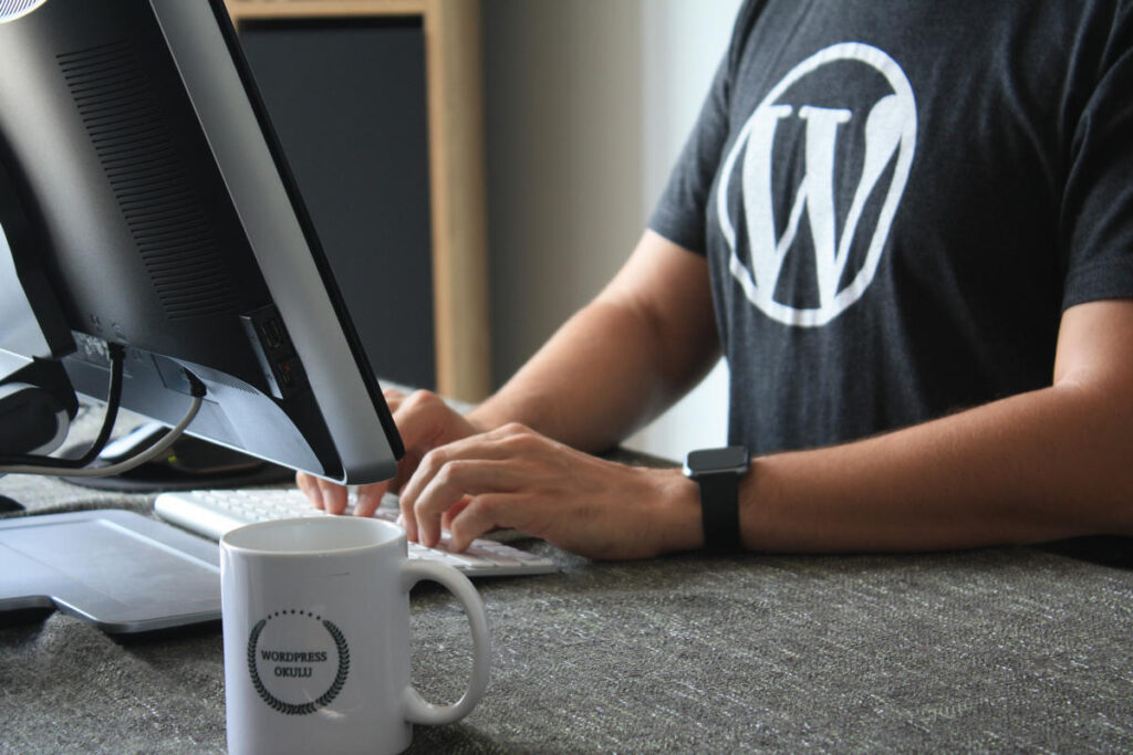 A man wearing a t-shirt with the WordPress logo sat at his computer screen