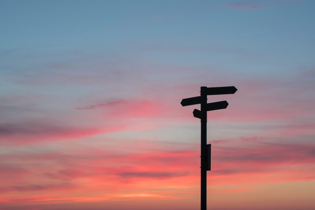 Silhouette of street sign against sunset background of orange clouds