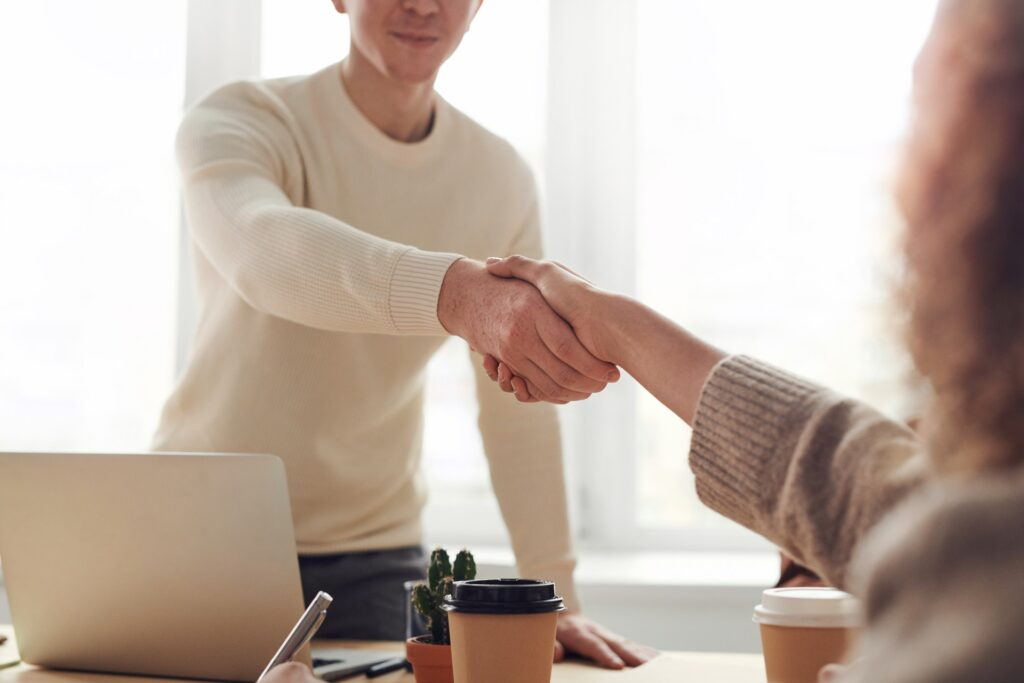 Two people shaking hands at an interview