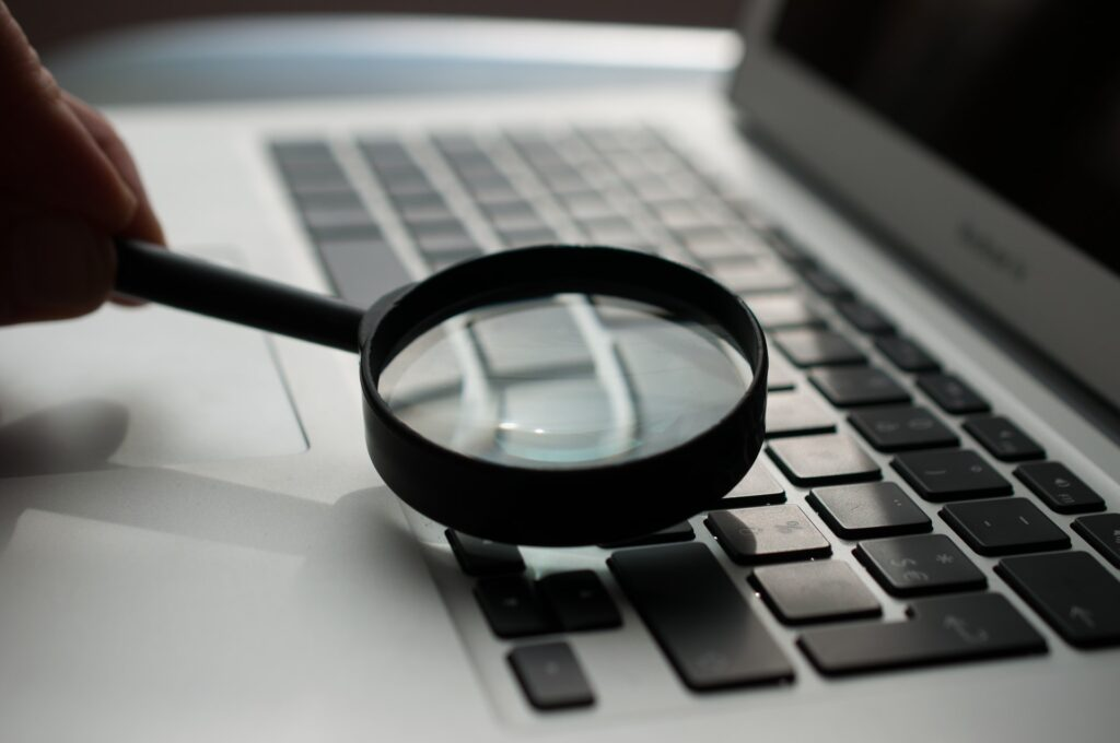 A magnifying glass being used on laptop keyboard to simulate scouring the internet
