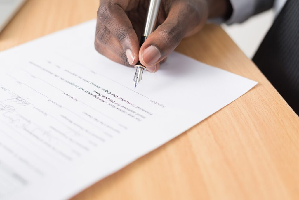 A man's hand with a pen, signing a contract