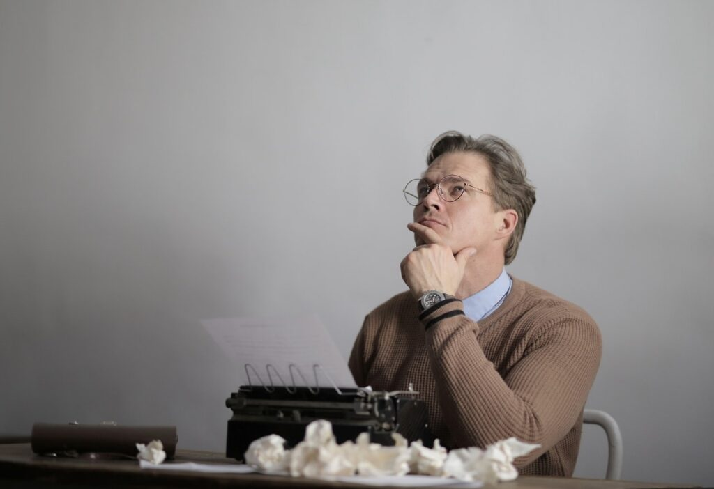Man sitting in front of typewriter with crumpled paper