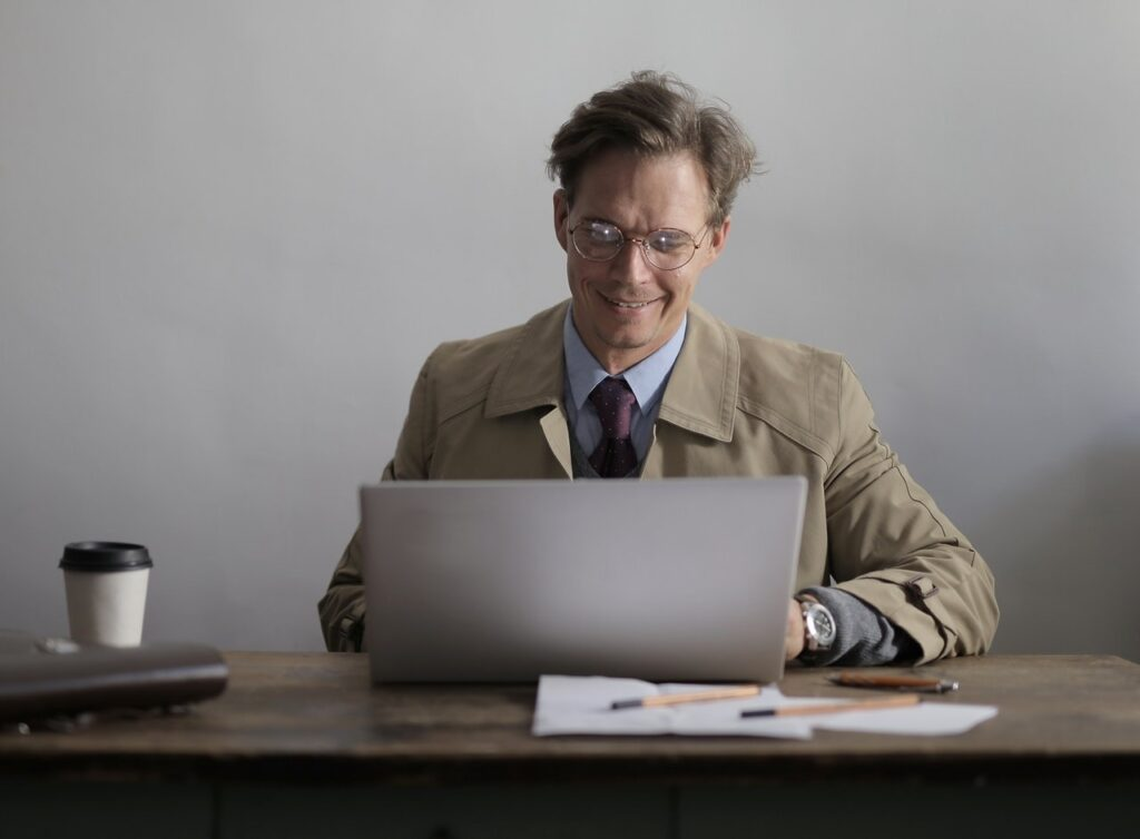 Man in a suit smiles while working on a laptop