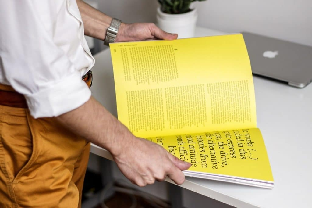 Man holding a yellow printed book