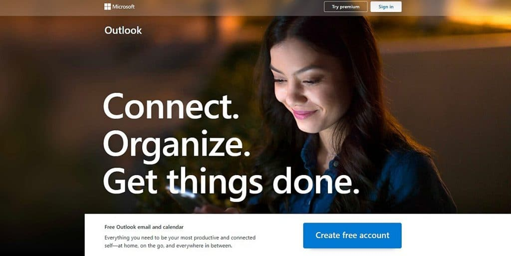 Microsoft Outlook calendar app homepage with a woman checking her smartphone