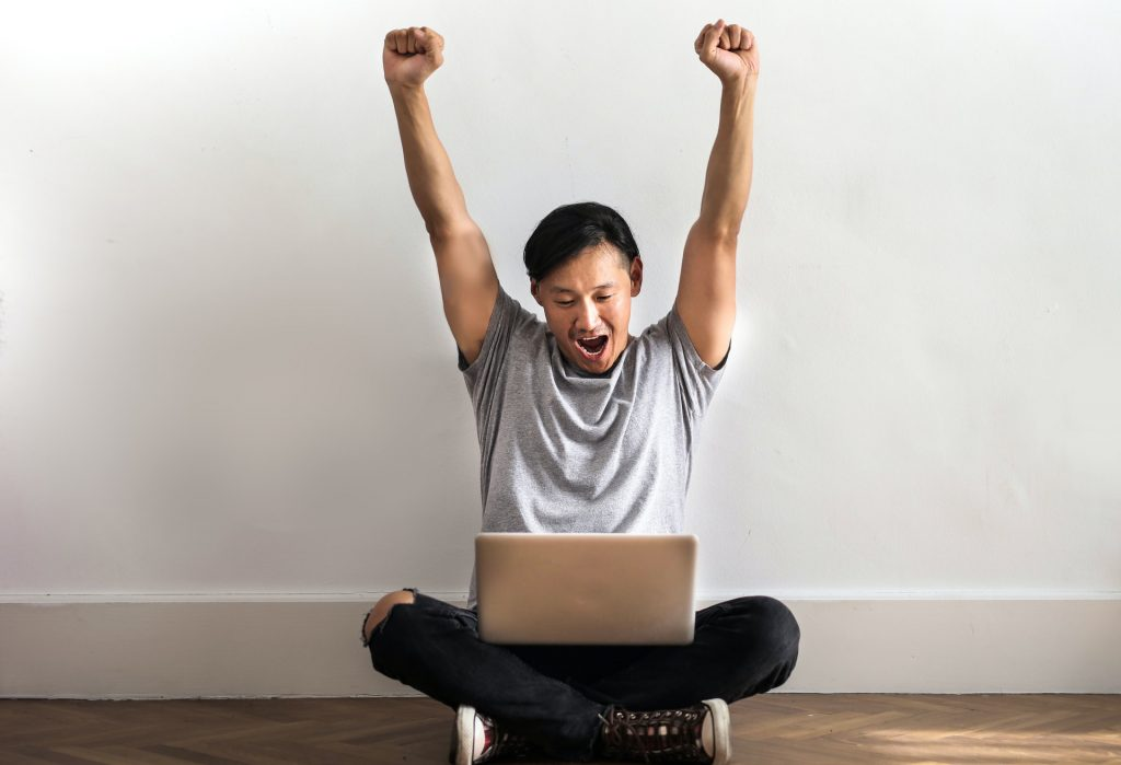 Man celebrating with fists raised in air sitting on floor with his laptop