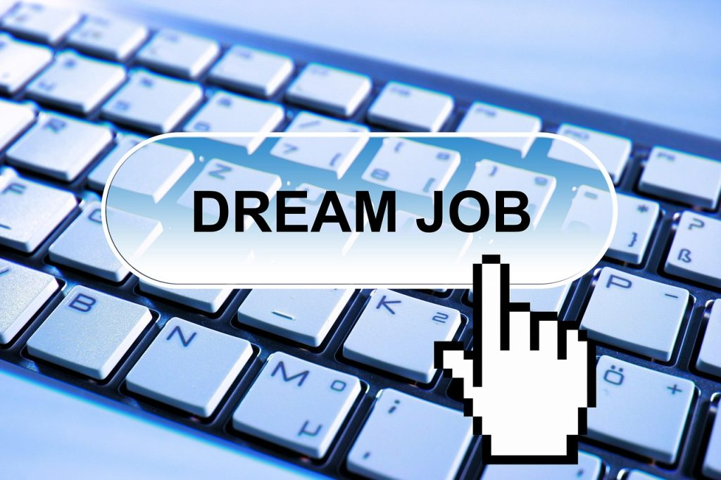 """Hand icon clicking on the words """"dream job"""" over a keyboard"""